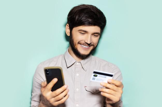 Ritratto di giovane ragazzo utilizza lo smartphone e la carta di credito su sfondo di colore aqua menthe