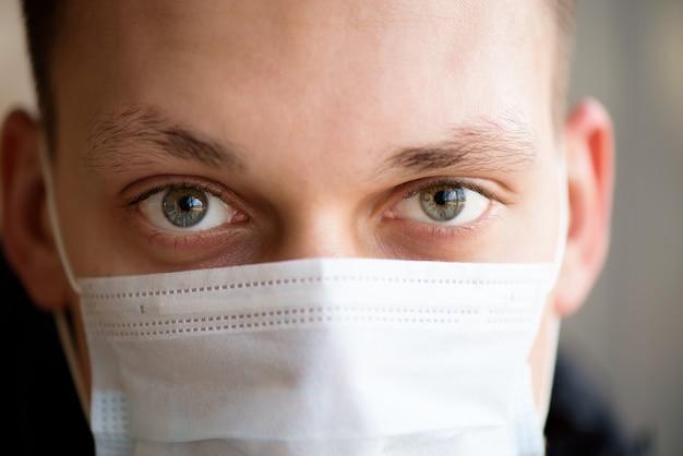 Ritratto di un giovane ragazzo che indossa una maschera di protezione contro il coronavirus in aeroporto