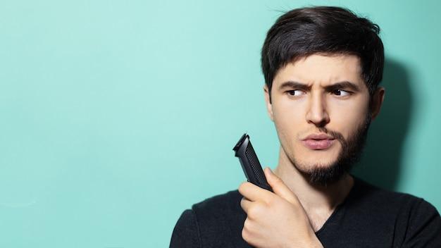 Ritratto di giovane ragazzo con metà faccia rasata tenendo in mano il trimmer