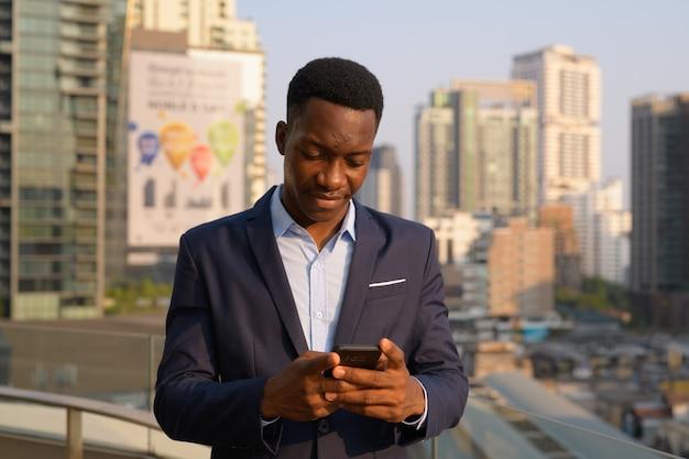 Ritratto di giovane uomo d'affari africano bello contro la vista della città