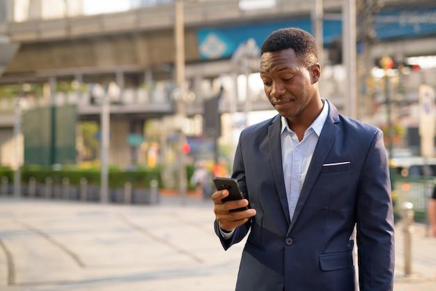 Ritratto di giovane uomo d'affari africano bello esplorare le strade della città di bangkok
