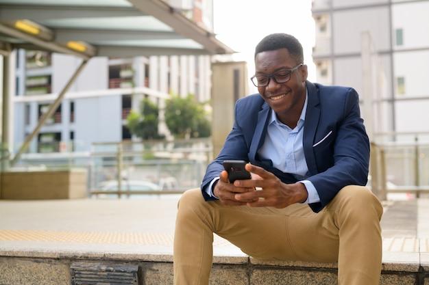 Ritratto di giovane uomo d'affari africano bello al di fuori della stazione ferroviaria della metropolitana