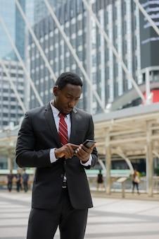 Ritratto di giovane uomo d'affari africano bello in vestito contro la vista di un edificio moderno nella città all'aperto