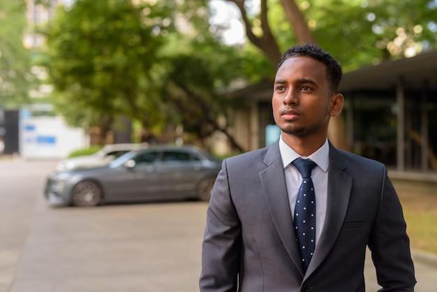 Ritratto di giovane uomo d'affari africano bello pensare all'aperto