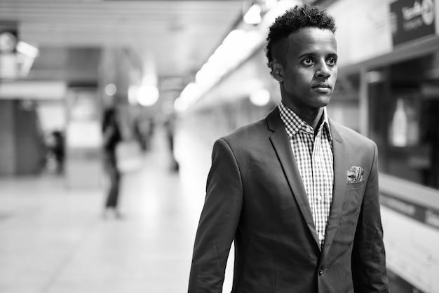 Ritratto di giovane uomo d'affari africano bello che indossa tuta alla stazione della metropolitana in bianco e nero
