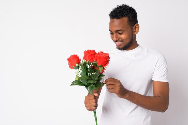 Ritratto di giovane uomo africano bello pronto per il giorno di san valentino contro il muro bianco