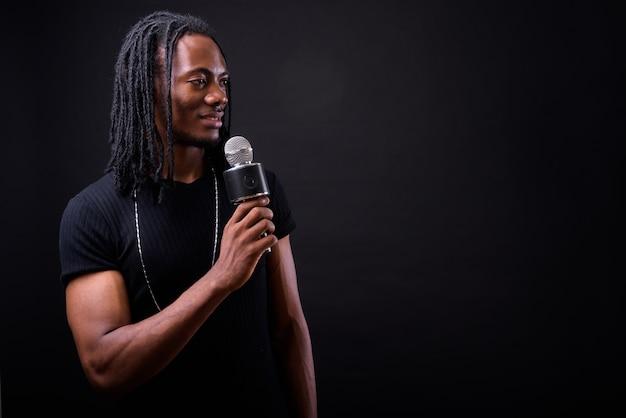 Ritratto di giovane uomo africano bello con i dreadlocks su fondo nero