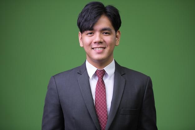 Ritratto di giovane uomo d'affari asiatico bello contro la chiave di crominanza con parete verde