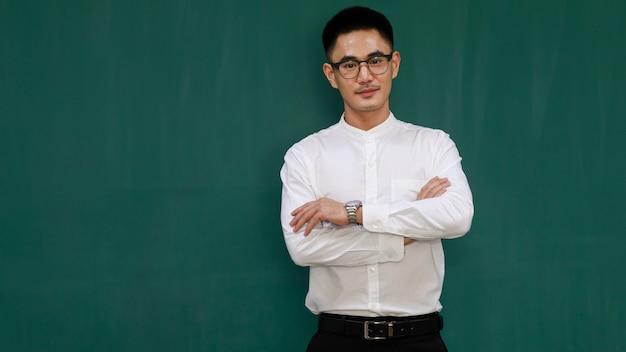 Ritratto di giovane e bell'uomo asiatico che indossa occhiali da vista e abiti da lavoro casual, camicia bianca e pantaloni neri, braccia incrociate con fiducia in se stessi con sfondo verde e copia spazio.