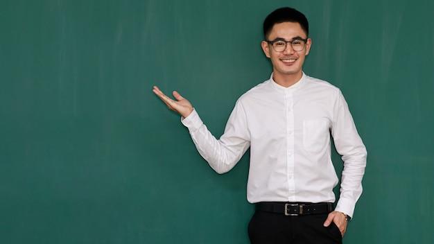 Ritratto di giovane e bell'uomo asiatico che indossa occhiali e abiti da lavoro casual, camicia bianca e pantaloni neri, posa in gesti di pubblicità e presenta qualcosa con fiducia in se stessi.