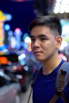 Ritratto di giovane bello turista asiatico uomo esplorando a chinatown a bangkok, in thailandia