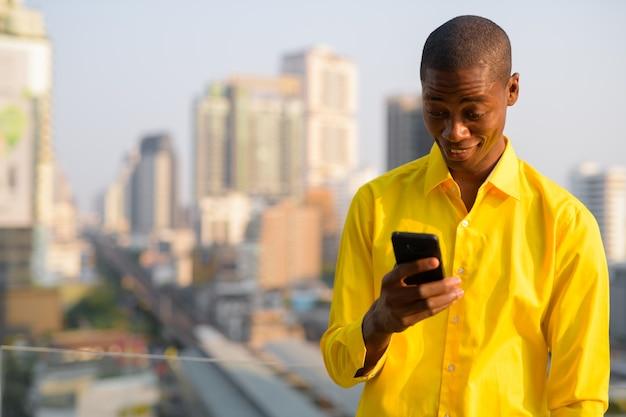 Ritratto di giovane uomo d'affari africano calvo bello contro la vista della città