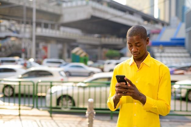 Ritratto di giovane uomo d'affari africano calvo bello esplorare le strade della città di bangkok