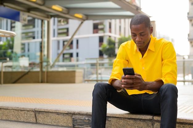 Ritratto di giovane uomo d'affari africano calvo bello fuori dalla stazione ferroviaria della metropolitana