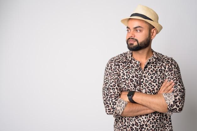 Ritratto di giovane uomo indiano barbuto bello contro il muro bianco