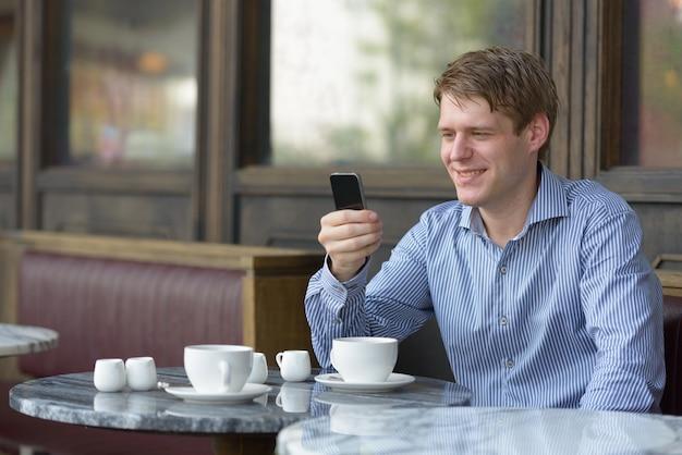 Ritratto di giovane uomo d'affari biondo bello rilassante presso la caffetteria all'aperto