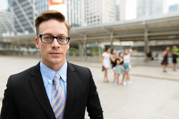 Ritratto di giovane uomo d'affari biondo bello in vestito al ponte dello skywalk nella città all'aperto