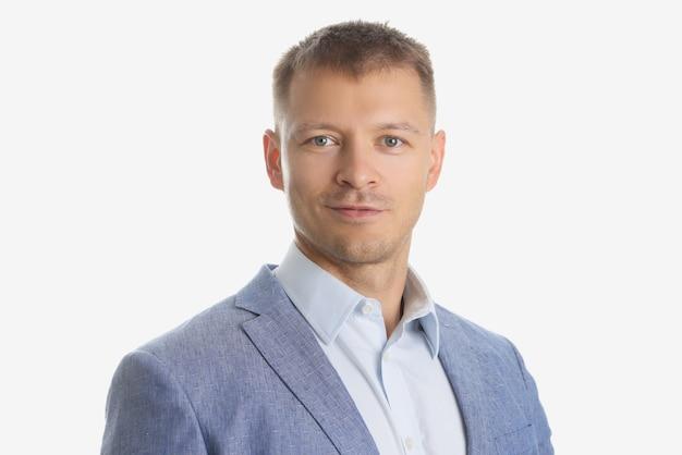 Ritratto di giovane uomo d'affari bello in abito grigio su sfondo bianco
