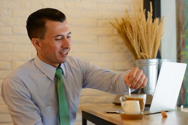 Ritratto di giovane uomo d'affari bello all'interno della caffetteria