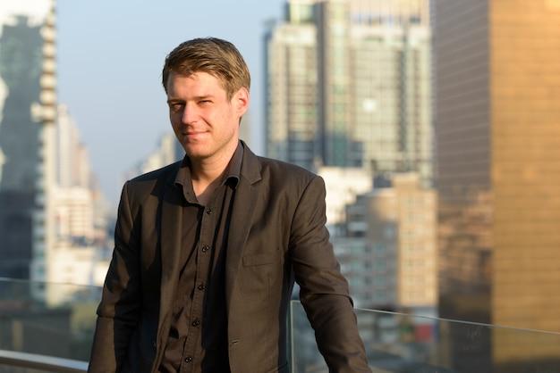 Ritratto di giovane uomo d'affari bello in vestito contro la vista della città