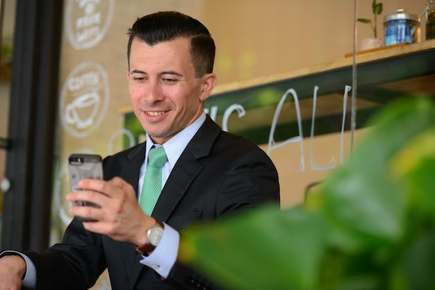Ritratto di giovane uomo d'affari bello in vestito presso la caffetteria all'aperto