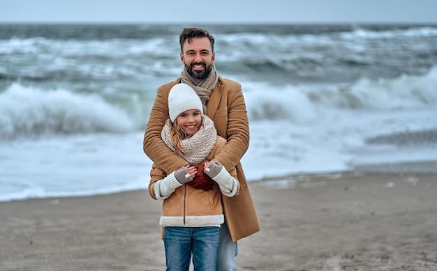 Ritratto di un giovane papà bello con la sua amata figlia carina sulla spiaggia in inverno.