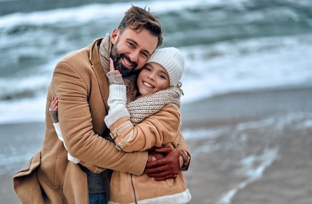 Ritratto di un giovane bel papà con la sua amata bella figlia sulla spiaggia in inverno.
