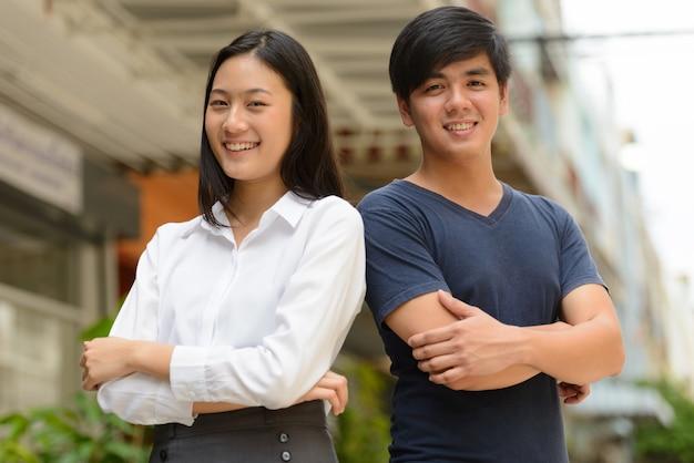 Ritratto di giovane uomo filippino bello e giovane bella donna asiatica insieme nelle strade all'aperto