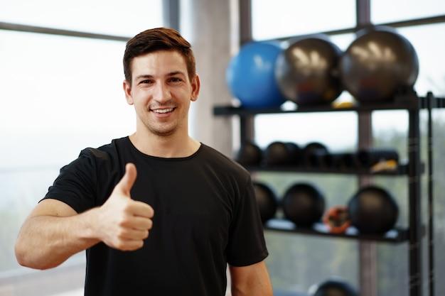 Ritratto di un giovane istruttore di fitness bello in una palestra