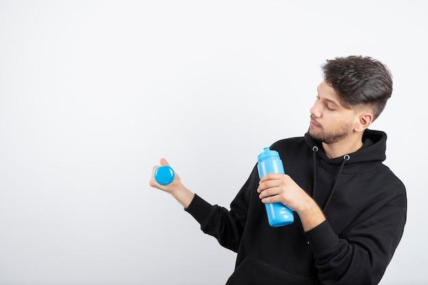 Ritratto di giovane bel ragazzo che tiene il manubrio blu e una bottiglia d'acqua
