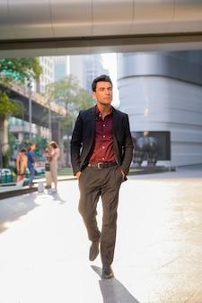 Ritratto di giovane uomo d'affari ispanico bello al di fuori dell'edificio per uffici