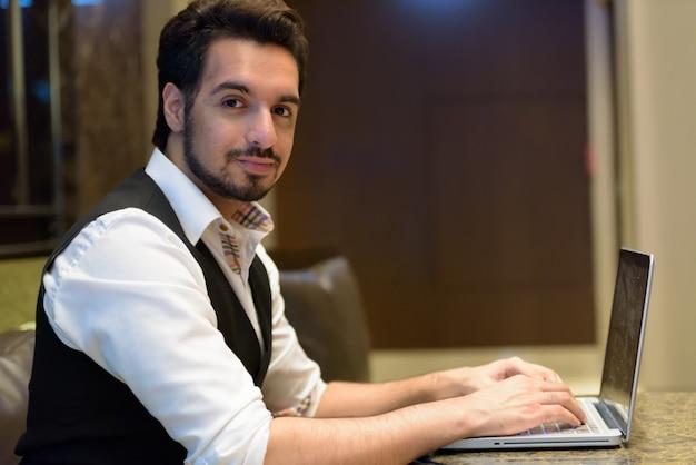 Ritratto di giovane uomo indiano bello utilizzando il computer portatile nella hall dell'hotel