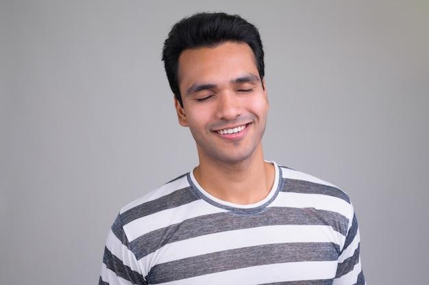 Ritratto di giovane uomo indiano bello su bianco