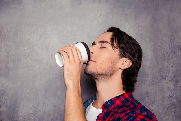 Ritratto di giovane uomo bello che beve caffè su uno spazio grigio