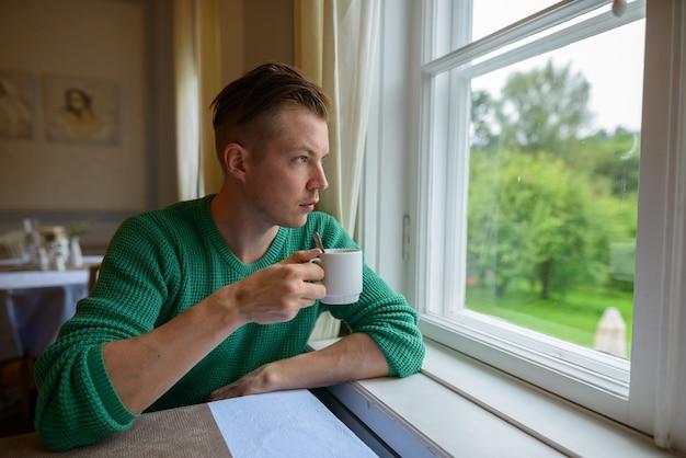 Ritratto di giovane uomo bello bere caffè e guardare fuori dalla finestra a casa