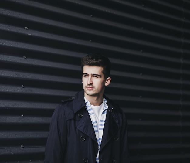 Ritratto di un giovane uomo bello, modello di moda, indossa una giacca