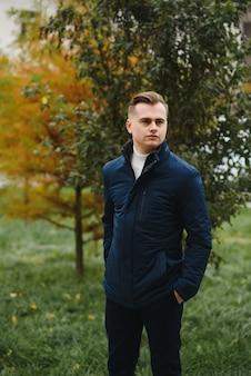 Ritratto di un giovane uomo bello, modello di moda, con acconciatura moderna in background urbano, indossando abiti casual.