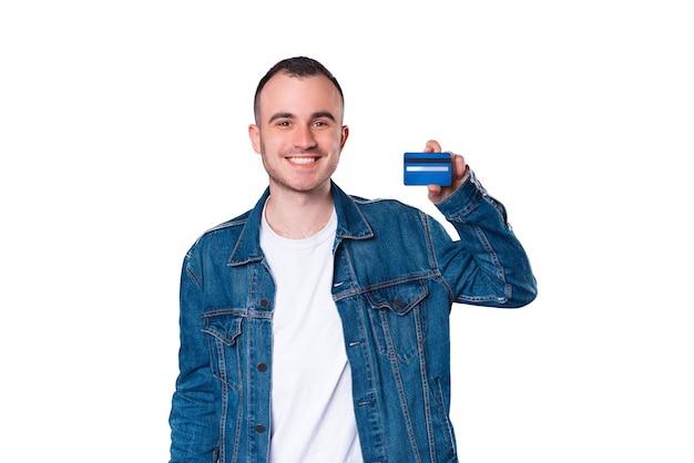 Ritratto di giovane uomo bello che sorride e che mostra la carta di credito blu