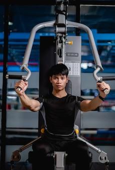 Ritratto giovane bell'uomo in abiti sportivi seduto per fare esercizio di pressa per il torace della macchina in palestra moderna,,