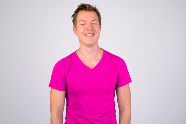 Ritratto di giovane uomo bello che indossa la camicia viola contro il muro bianco