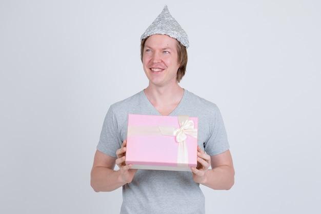 Ritratto di giovane uomo bello che indossa il cappello di latta come concetto di teoria del complotto su bianco