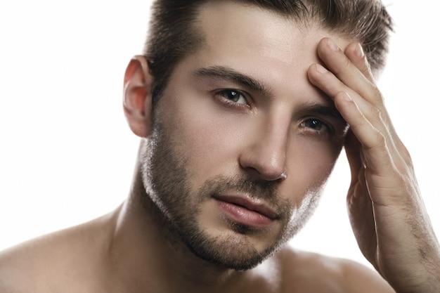 Ritratto di giovane uomo bello su sfondo bianco