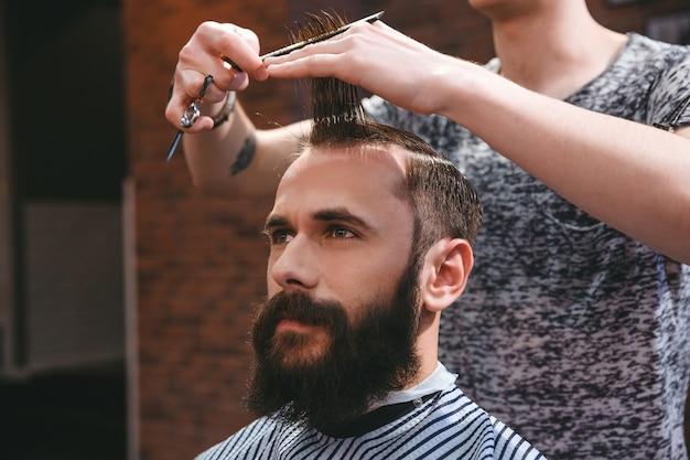 Ritratto di giovane uomo bello con la barba che ha un taglio di capelli con pettine e forbici nel parrucchiere