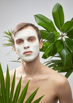 Ritratto di giovane uomo bello con maschera cosmetica bianca sul viso sullo sfondo di piante verdi. cura del viso maschile