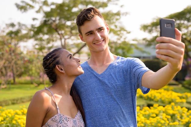Ritratto di giovane uomo bello e giovane bella donna asiatica rilassante insieme al parco