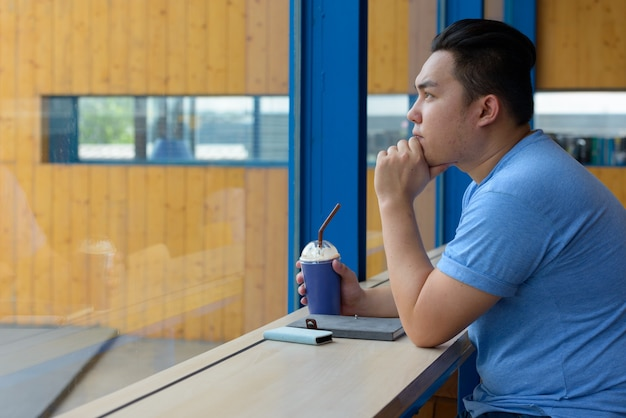 Ritratto di giovane uomo filippino in sovrappeso bello rilassante presso la caffetteria