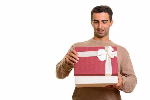 Ritratto di giovane uomo persiano bello che tiene confezione regalo