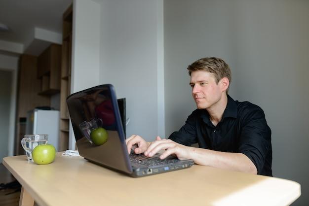 Ritratto di giovane uomo d'affari scandinavo bello con capelli biondi a casa al chiuso