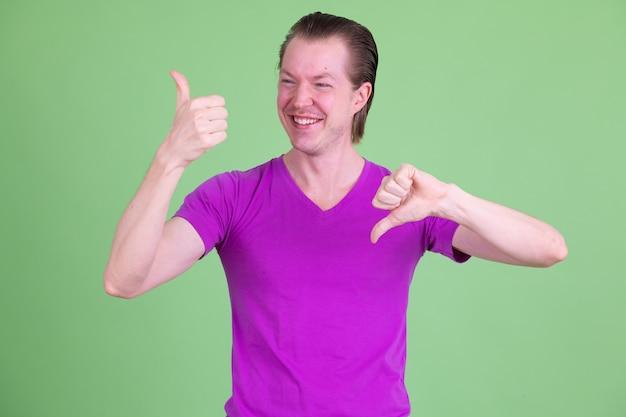 Ritratto di giovane uomo scandinavo bello che indossa la camicia viola contro la chiave di crominanza o la parete verde