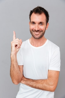 Ritratto di giovane bello carismatico sorridente che ha un'idea e punta il dito verso l'alto isolato su uno sfondo grigio